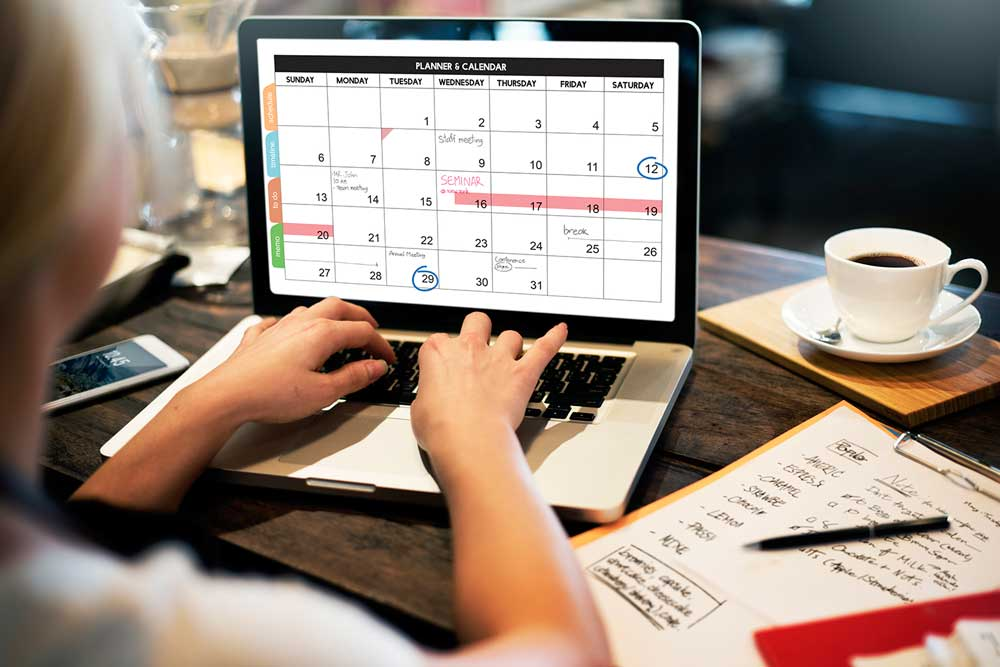 event planner creating a schedule on laptop