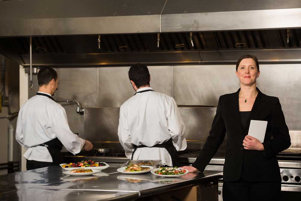 catering event planner in kitchen with chefs
