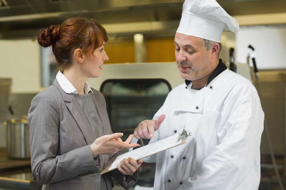 event planner discussing food & beverage with chef