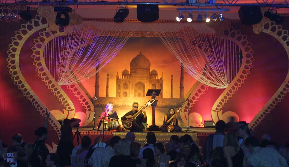 indian sitar players on stage with taj mahal backdrop